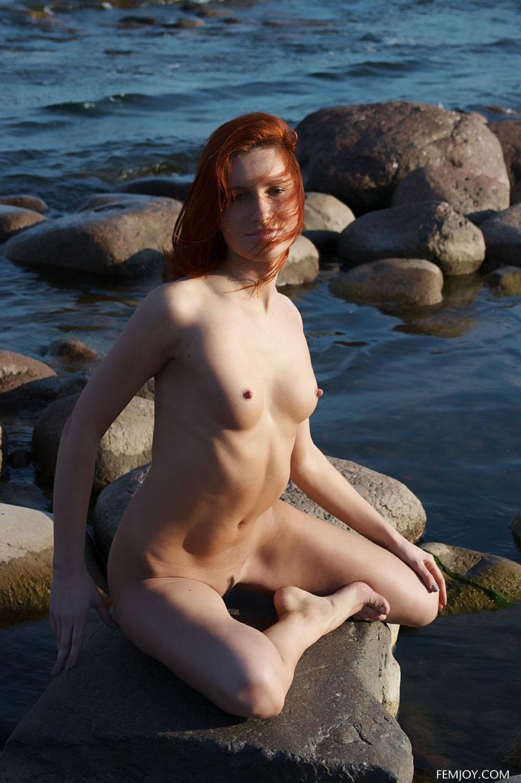 Молодая рыжая девушка голая на камнях