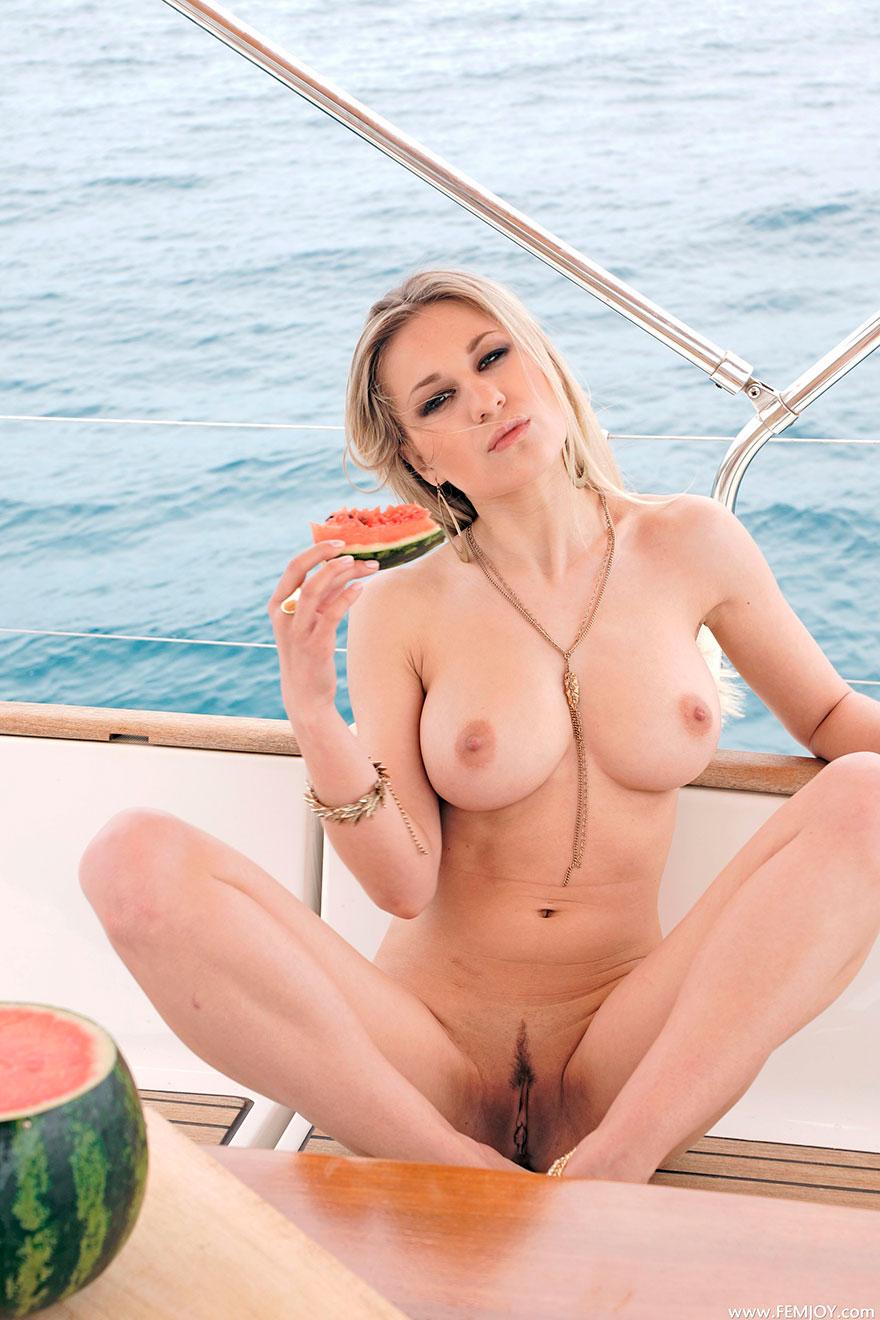 Модель со свелыми волосами на яхте поливает свои большие буфера шампанским