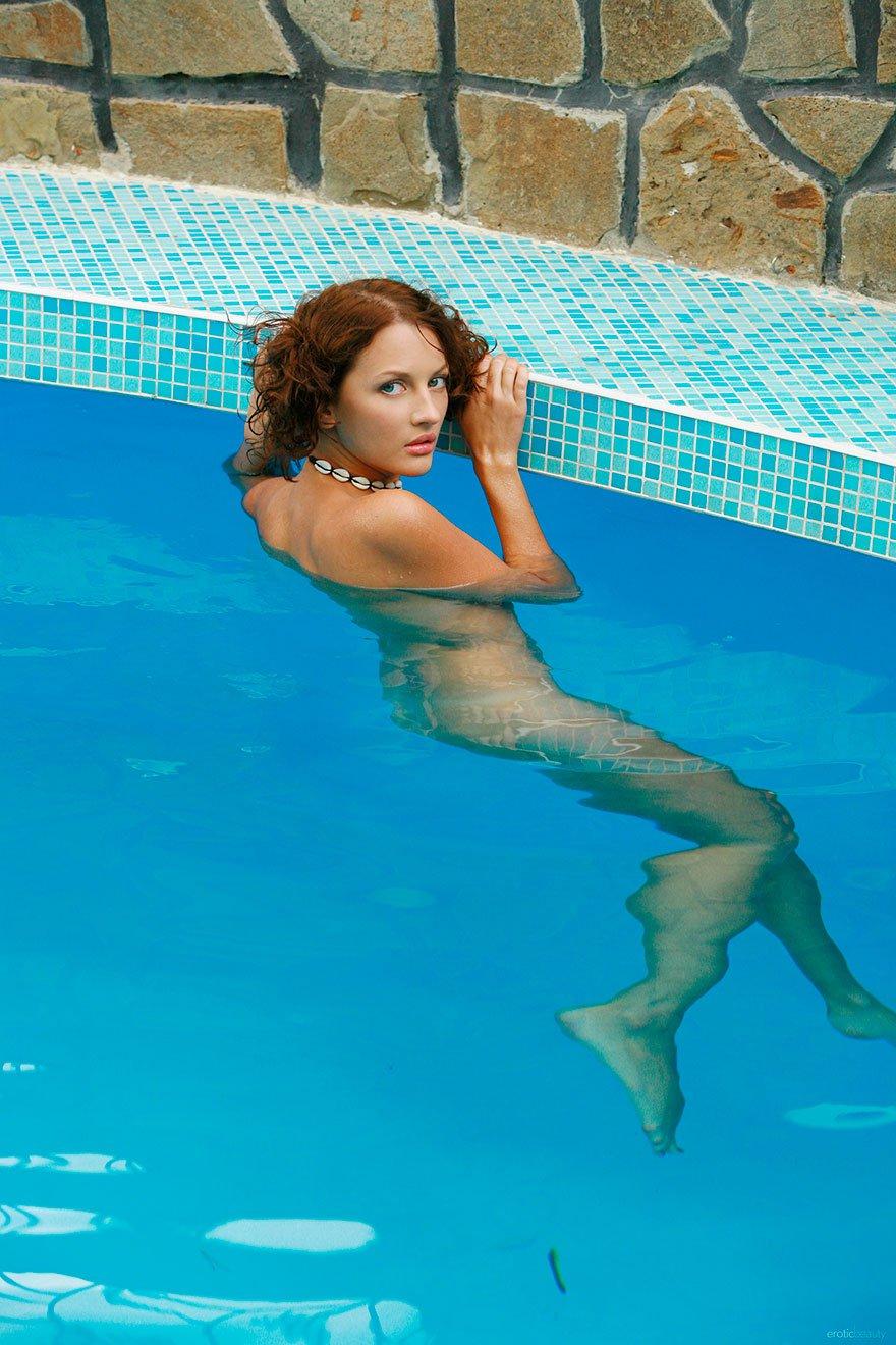Молодая чика плескается обнаженная в бассейне