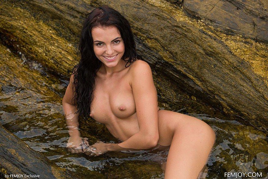 Фото брюнетки в серебристом купальнике на скалистом берегу