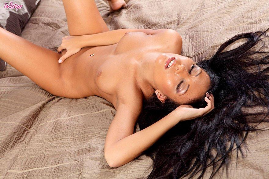 Фотки эротики загорелой брюнеточки в темном купальнике на широкой лежанки