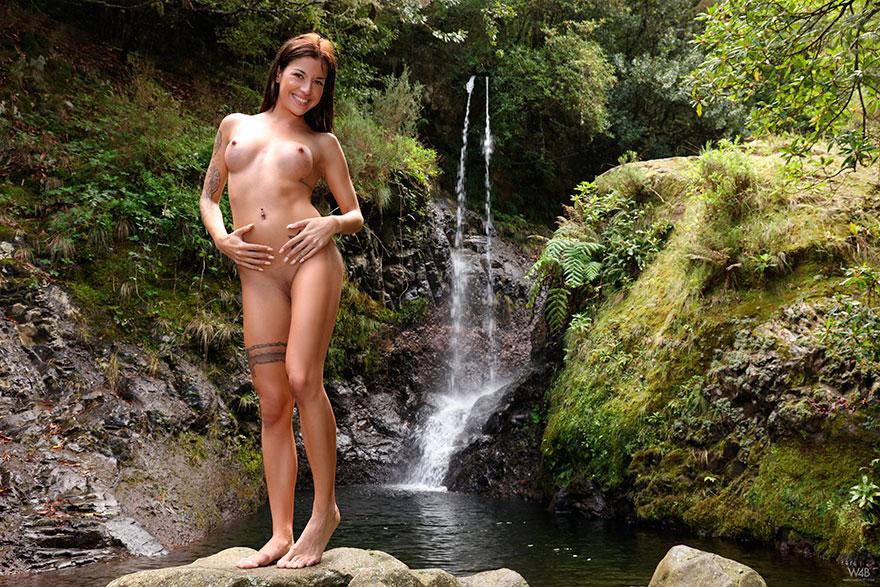 Шатенка с наколками круто фоткается на фоне водопада
