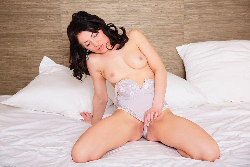 Эротические фото брюнетки с небесными глазами на лежанке секс фото