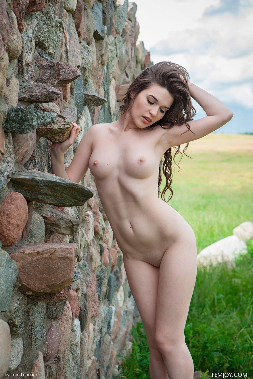 Красивая кобыла прижимается обнаженной жопой к каменной стене
