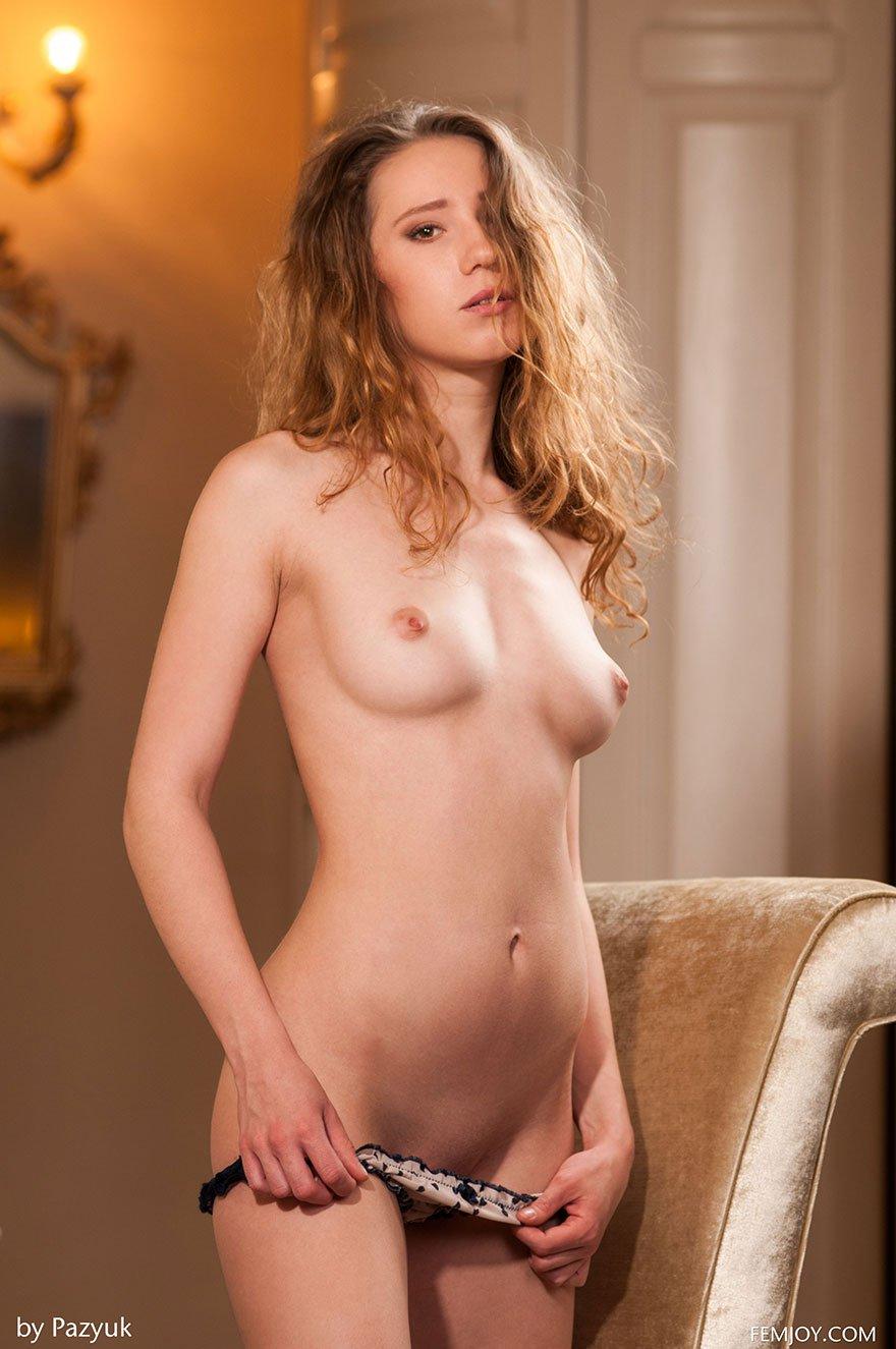 Обнаженная девушка с волнистыми волосами голая за столом