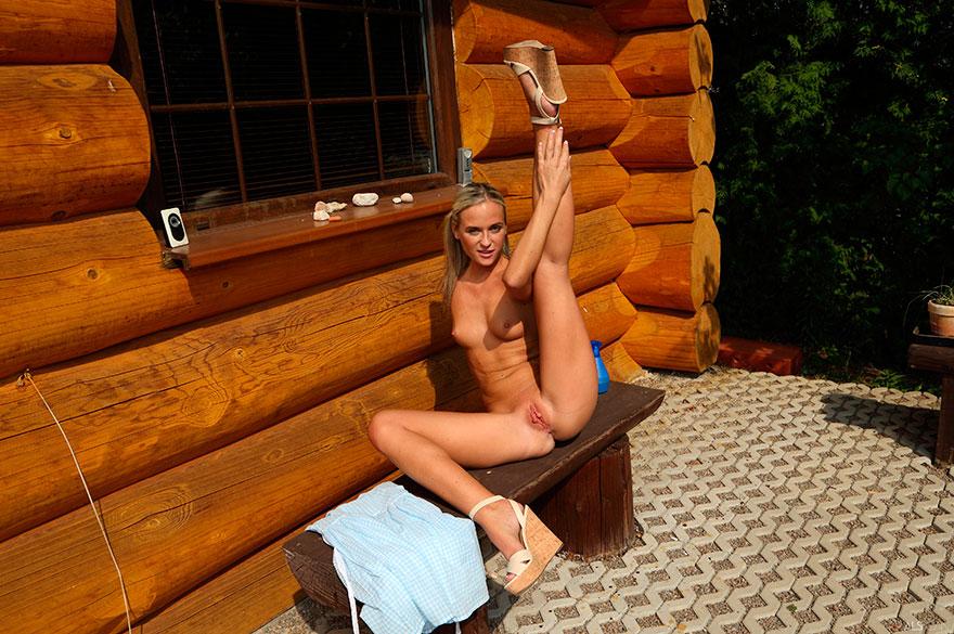 Откровенная эротика блондинки возле бревенчатой избушки