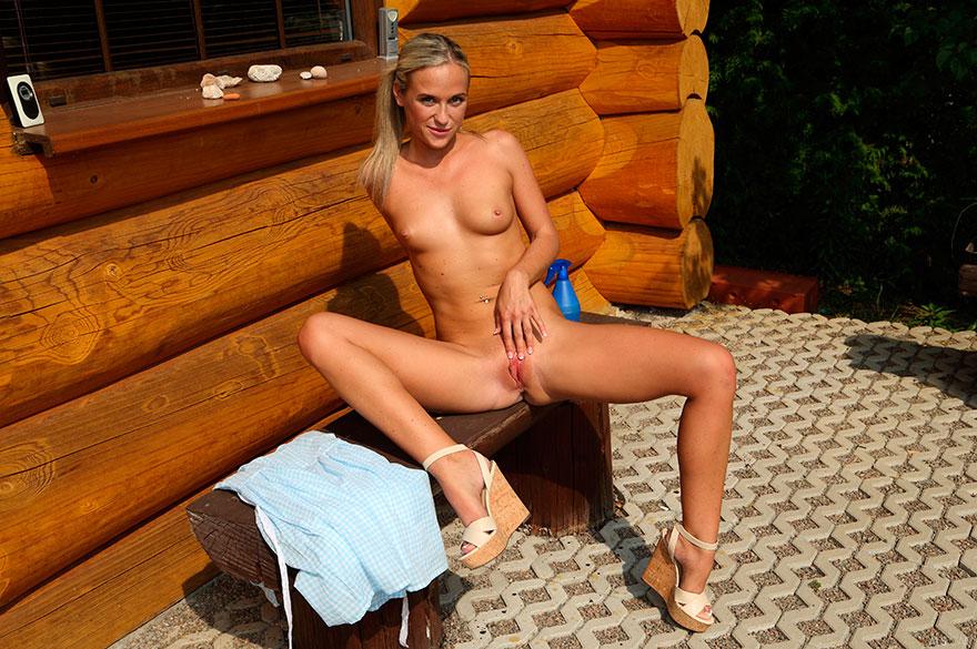 Страстная обнаженка блондиночки возле бревенчатой избушки