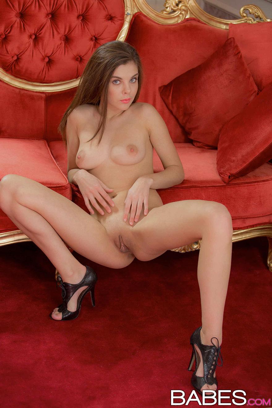 Эротические фото брюнетки на красном диванчике