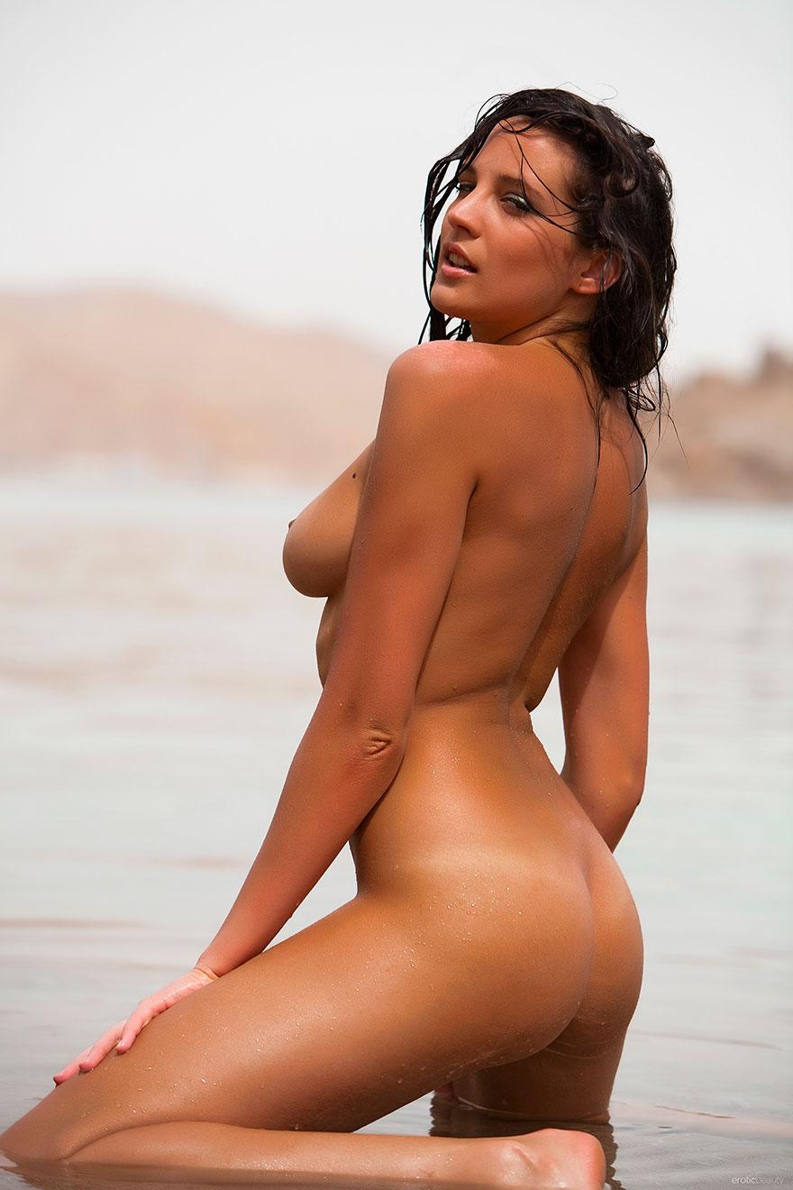Загорелая брюнетка плавает голая в море