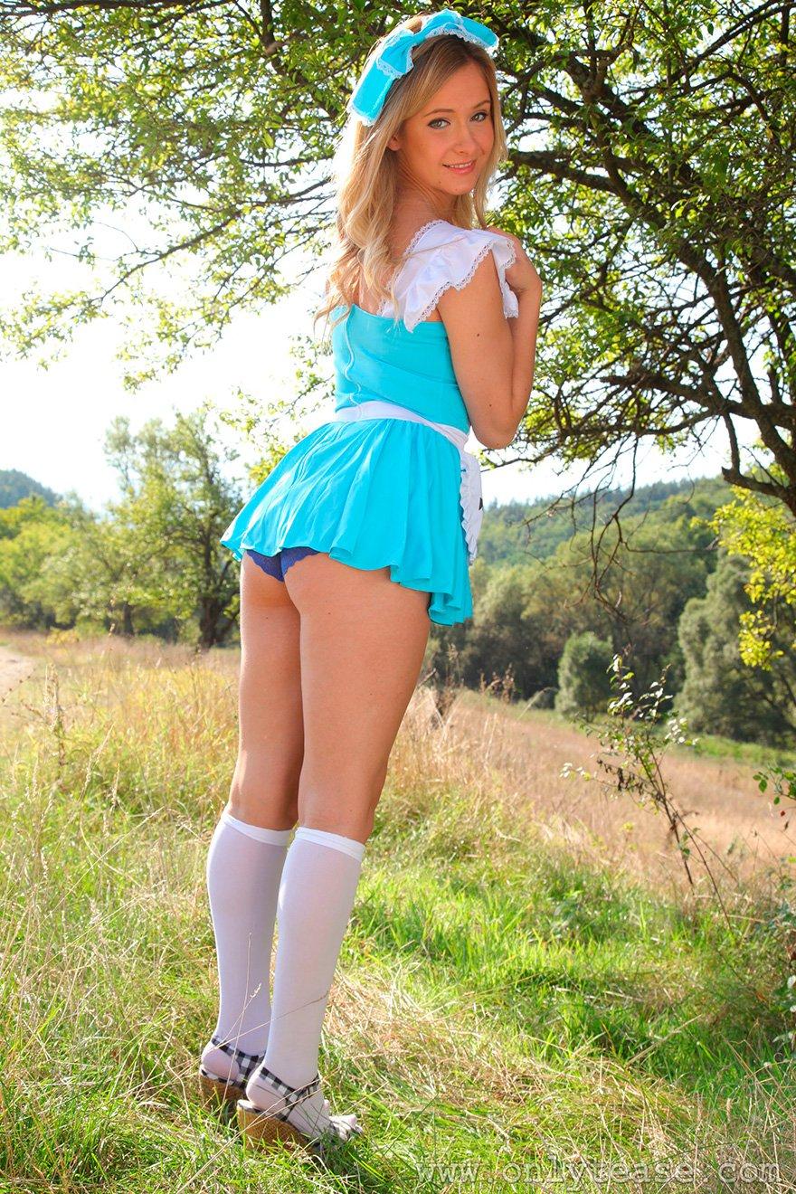Светловолосая девушка в возбуждающем наряде бродит на лугу