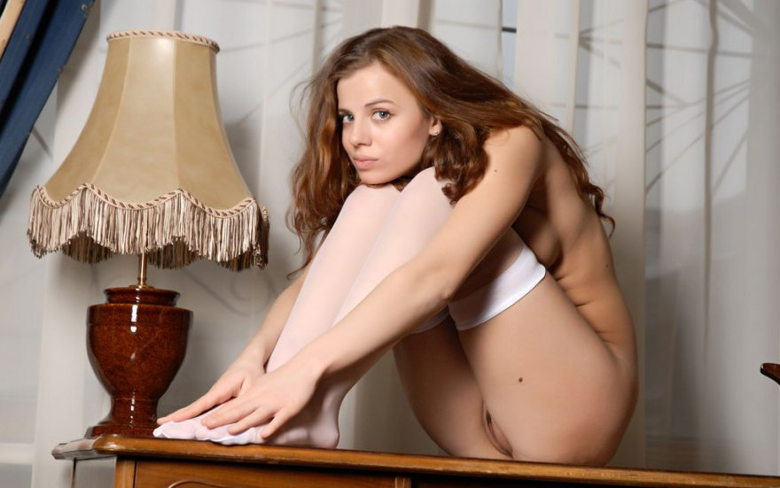 Молодая девушка в белых чулочках позирует в спальне
