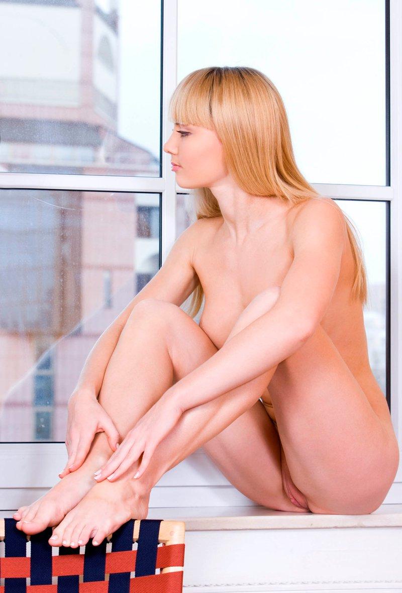 Эротика обнаженной блондинки на подоконнике