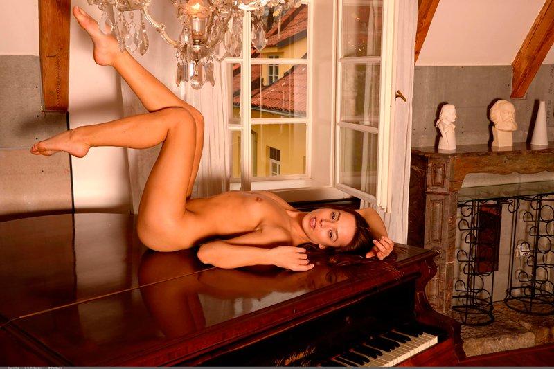 Эротика обнаженной девушки за роялем