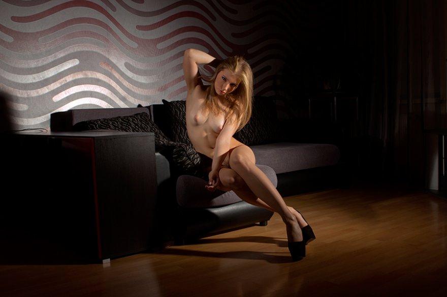 Голая блондинка в темной комнате