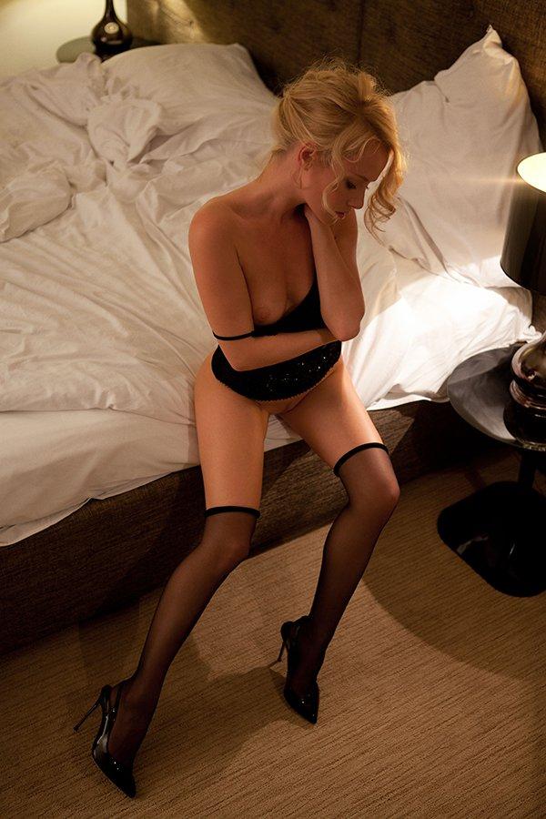 Раскрепощенная блондинка в чёрных чулках