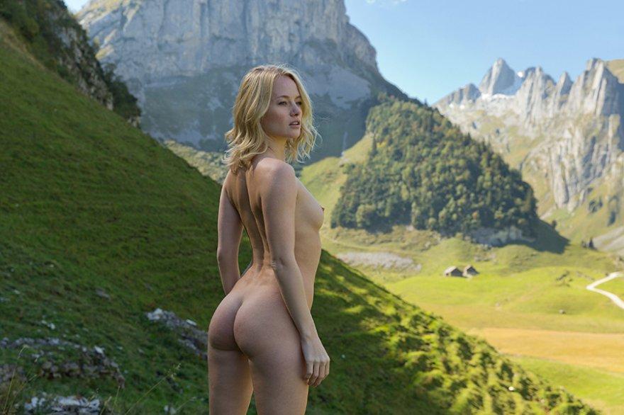Обнаженная модель со свелыми волосами спускает платье в горах
