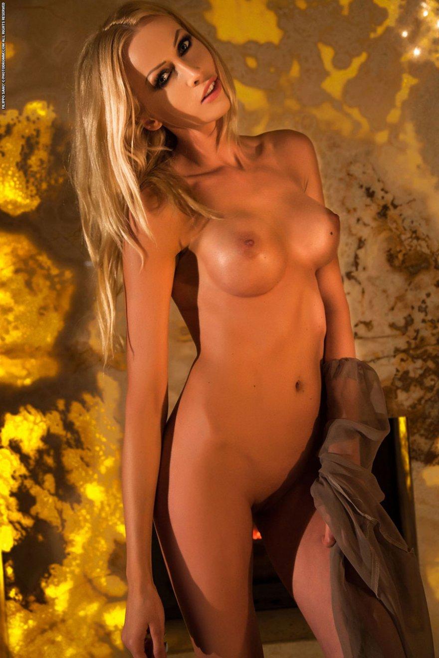Светловолосая девушка с симпатичными буферами раздевается возле камина