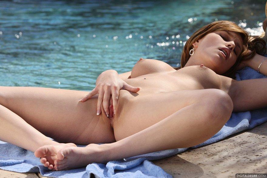 Молодая девушка снимает купальник и позирует возле пруда