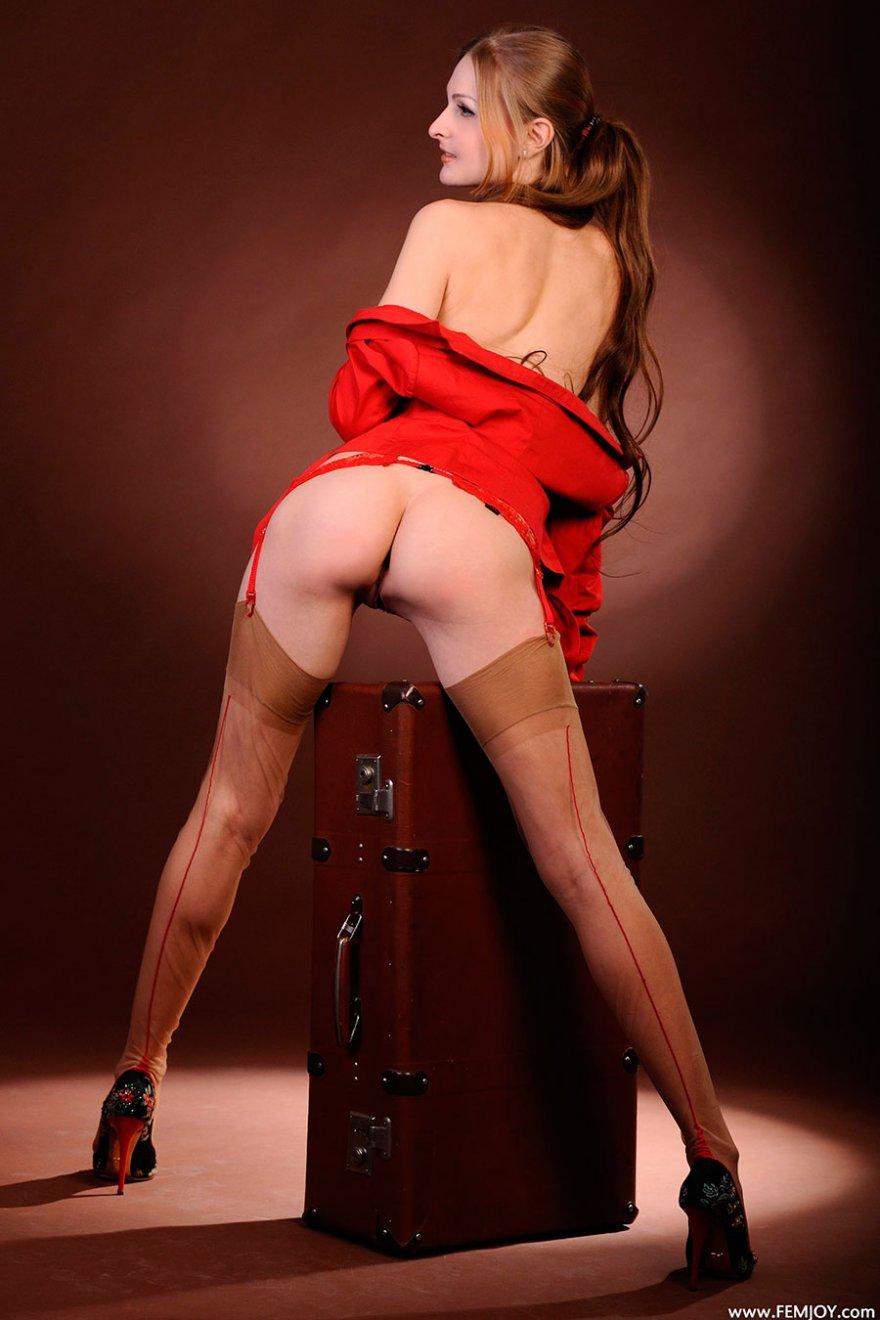 Девица в чулках с поясом позирует на старом чемодане