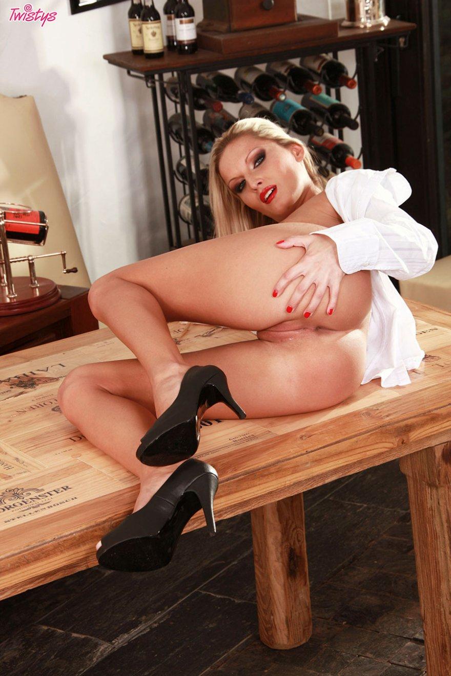 Сексуальная блондинка с фаллоимитатором на деревянном столе