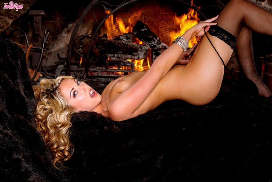 Хорошенькая клубничка блондинки на фоне камина
