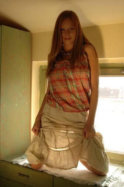 Девушка в длинной юбке сидит на подоконнике