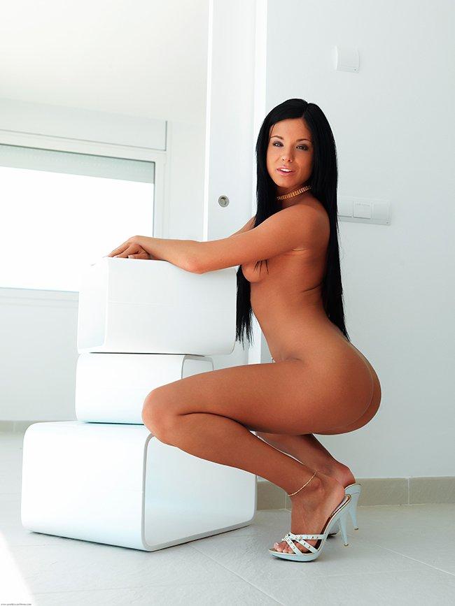 Красивая брюнетка с длинными волосами в белой комнате