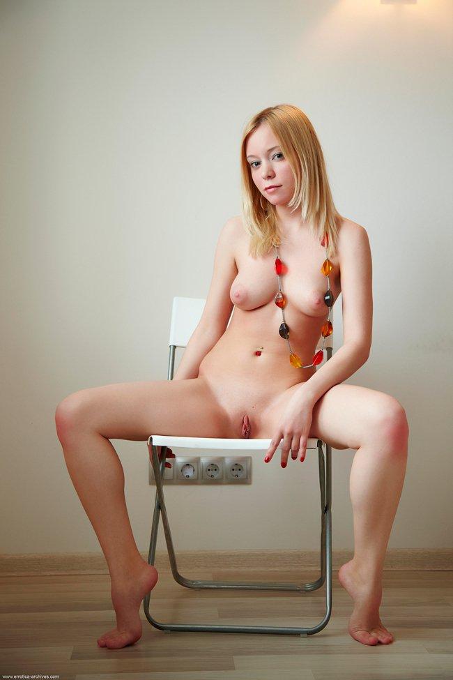 Блондинка с цветными бусами позирует на полу