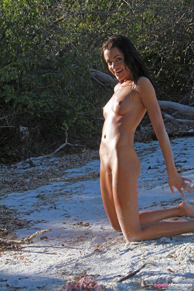 Обнажённая девушка на белом песке у моря