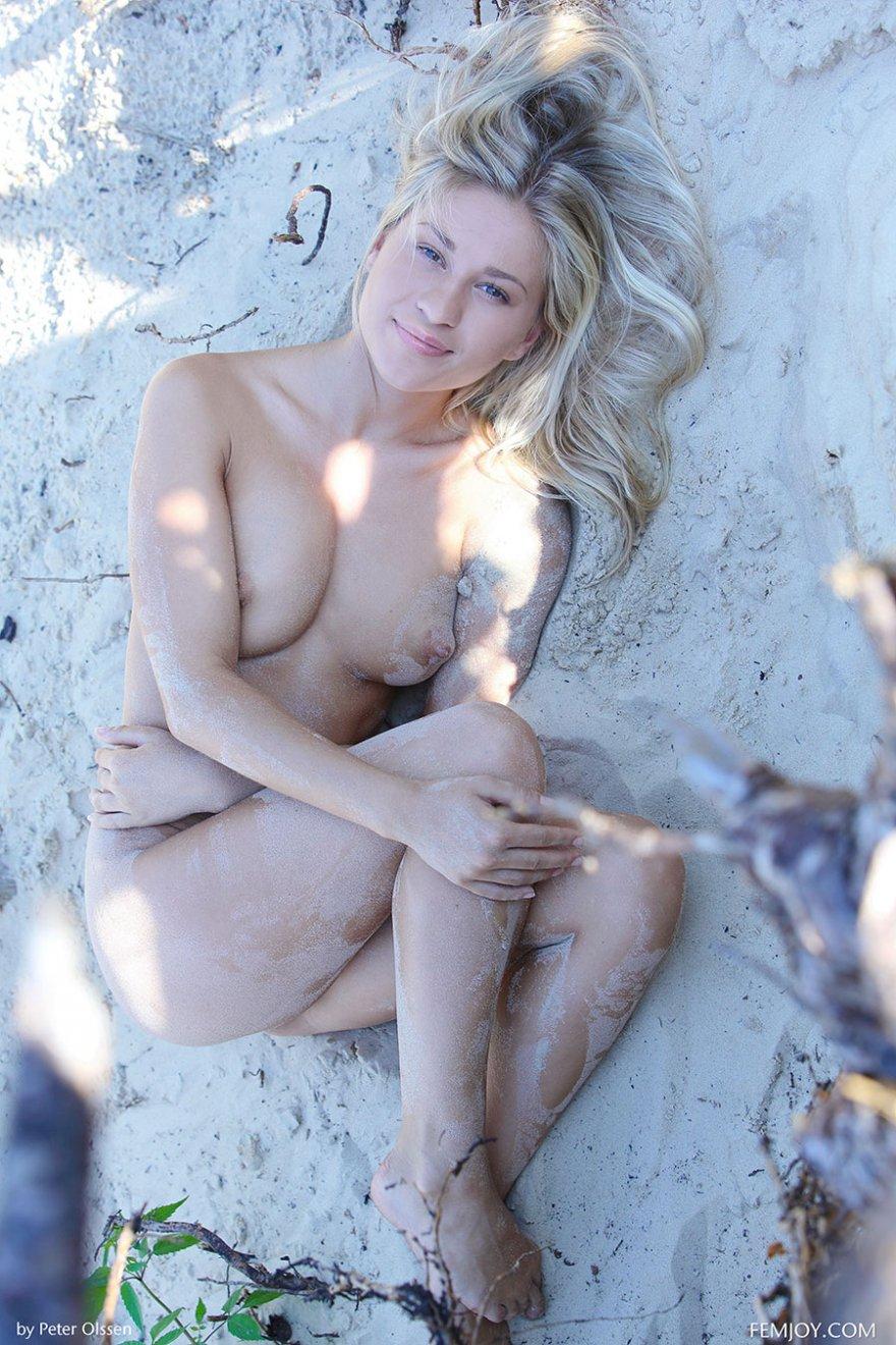 Обнаженная светловолосая девушка на белом песке