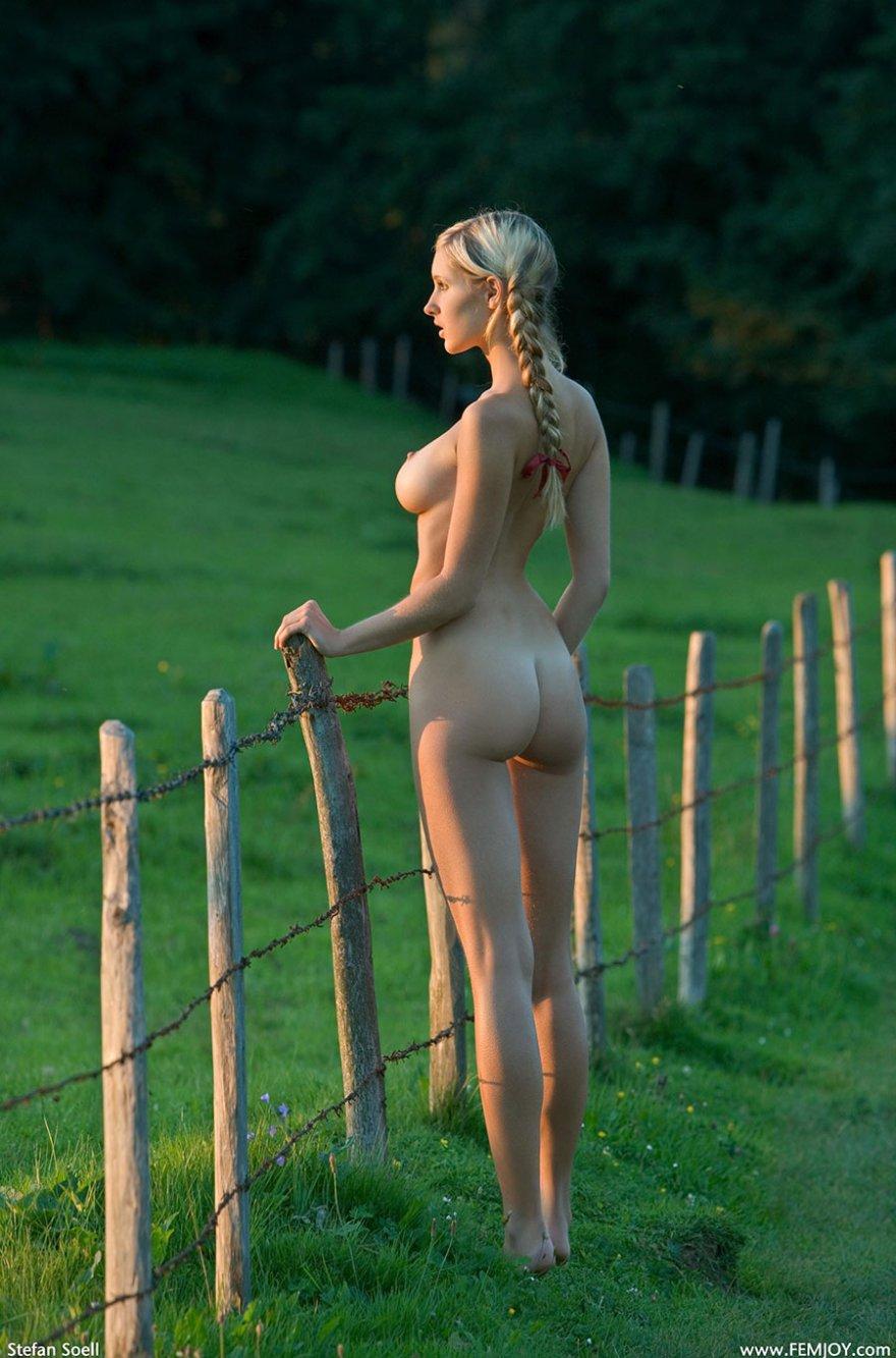 Раздетая светловолосая девушка с косичками на лугу