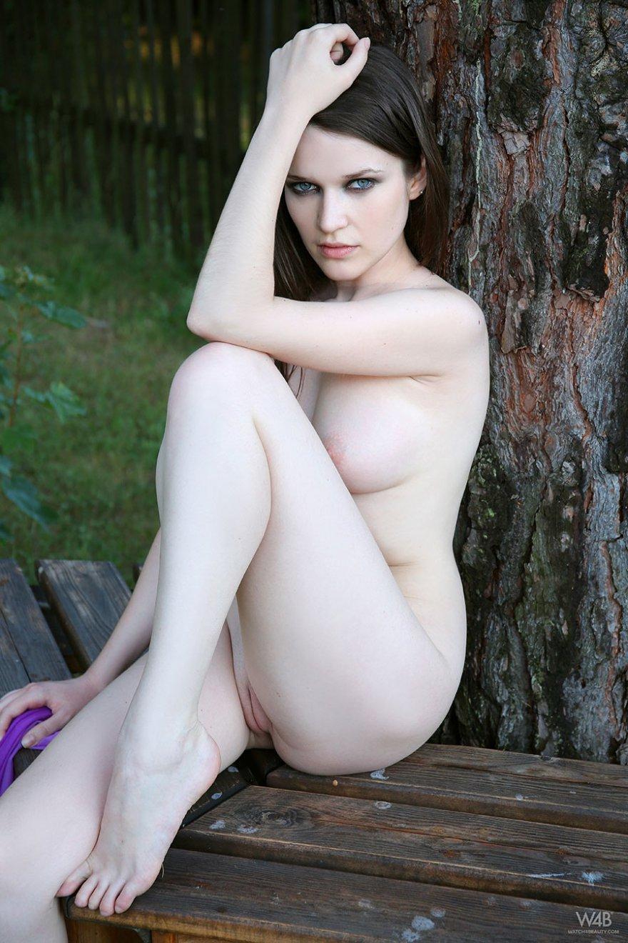 Стройные секс-фото голенькой брюнеточки на скамейке под деревом