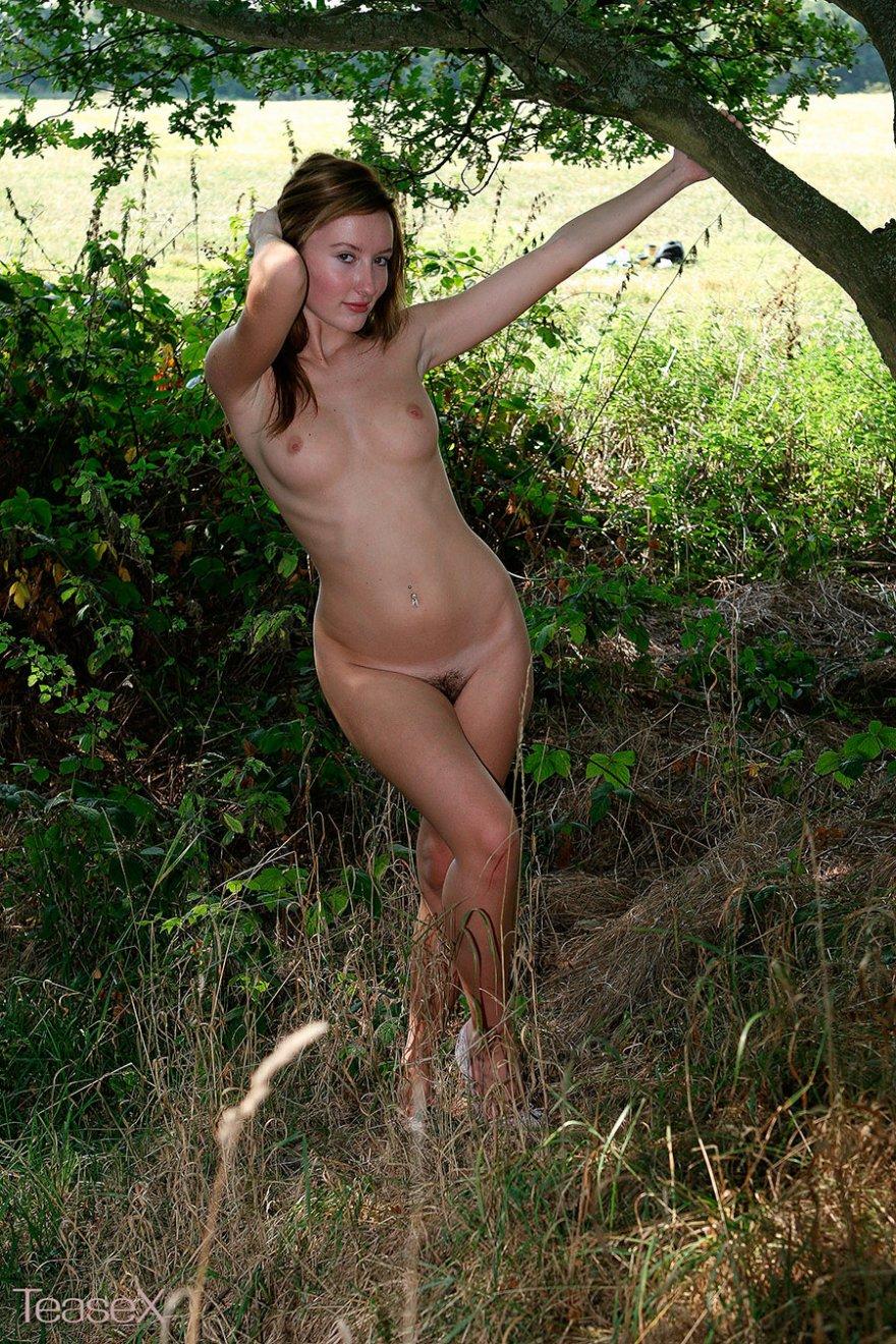 Рыжая девушка в трусиках позирует на поляне
