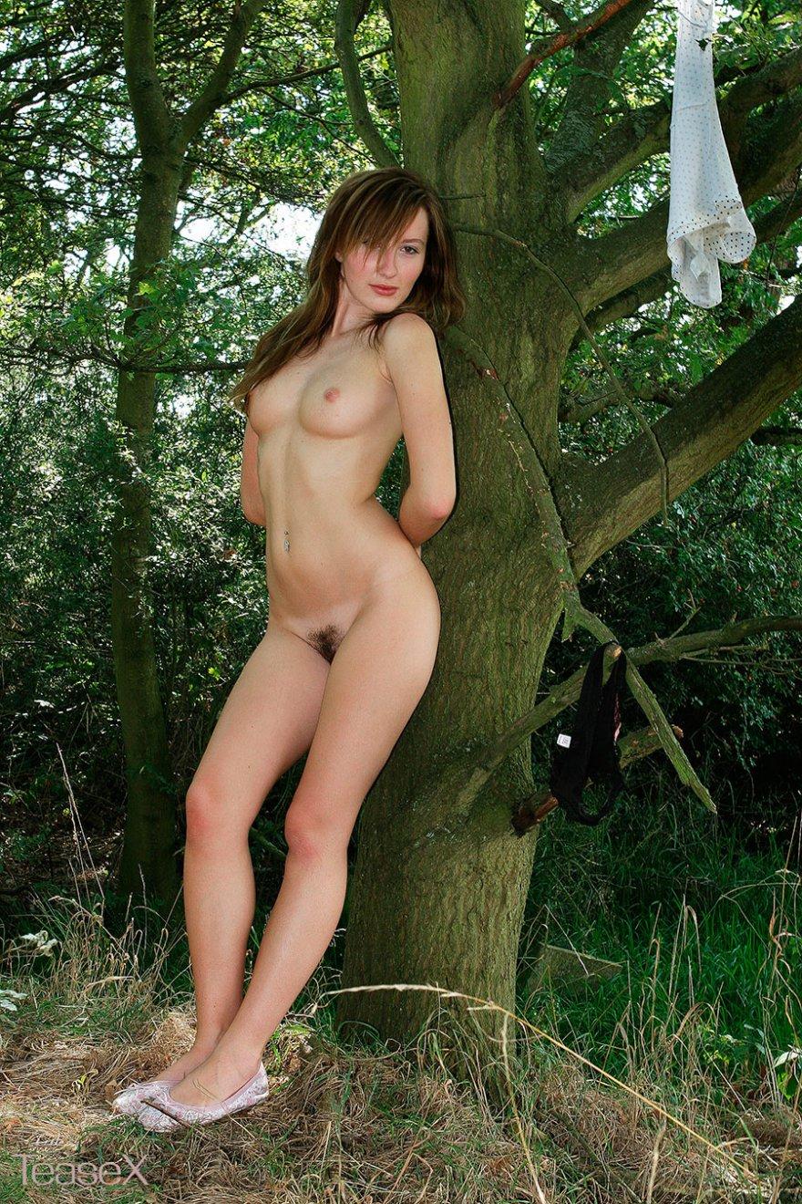 Рыженькая девка в бикини позирует на природе