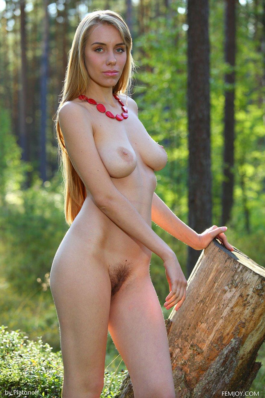 Модель со свелыми волосами без одежды гуляет в лесу