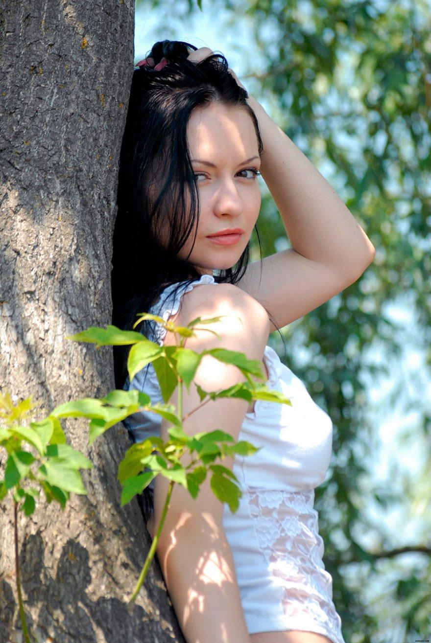 Очаровательная брюнетка в кружевном белье сидит на дереве