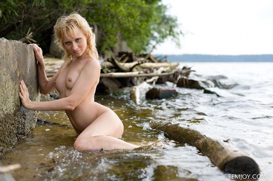 Нагая блондиночка на камнях