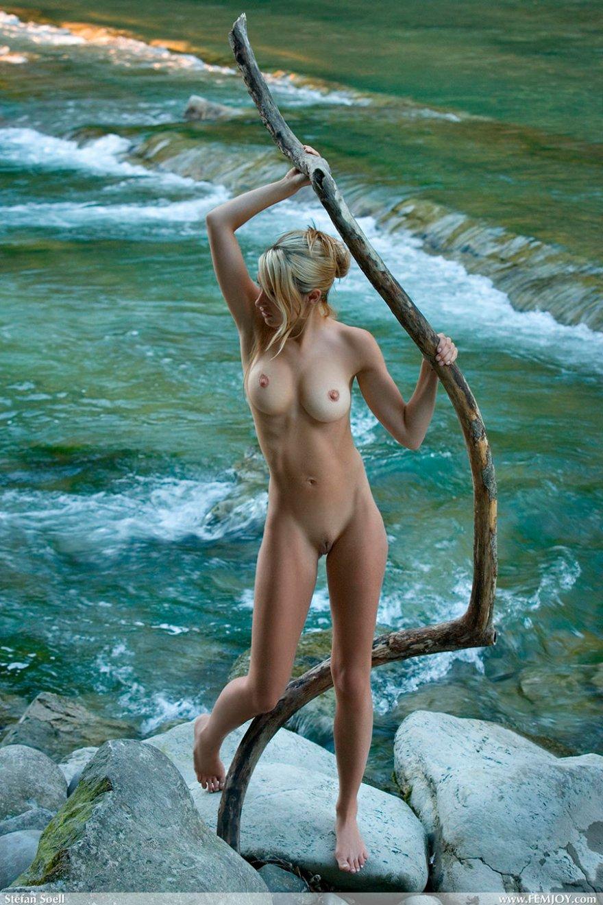 Светловолосая девушка с красивой фигуркой на фоне реки