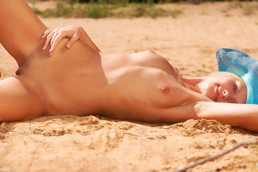 Чистая светловолосая девушка в голубой шляпе делает селфи у моря