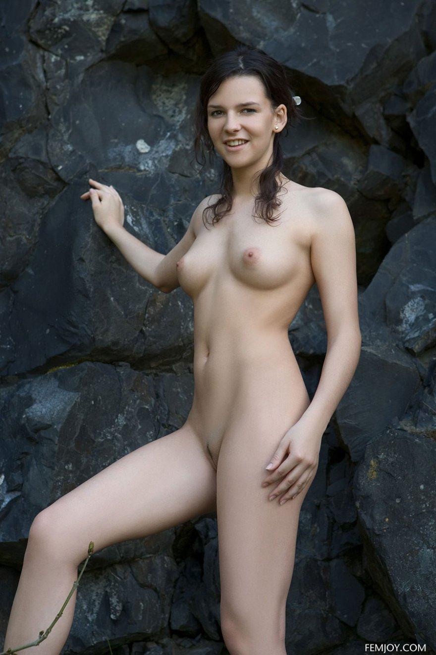 Привлекательная раздетая модель с темными волосами недалеко от черной скалы