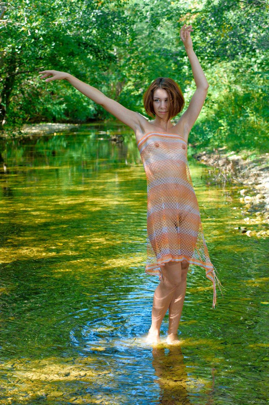 Молодая девушка с сетью на берегу ручья