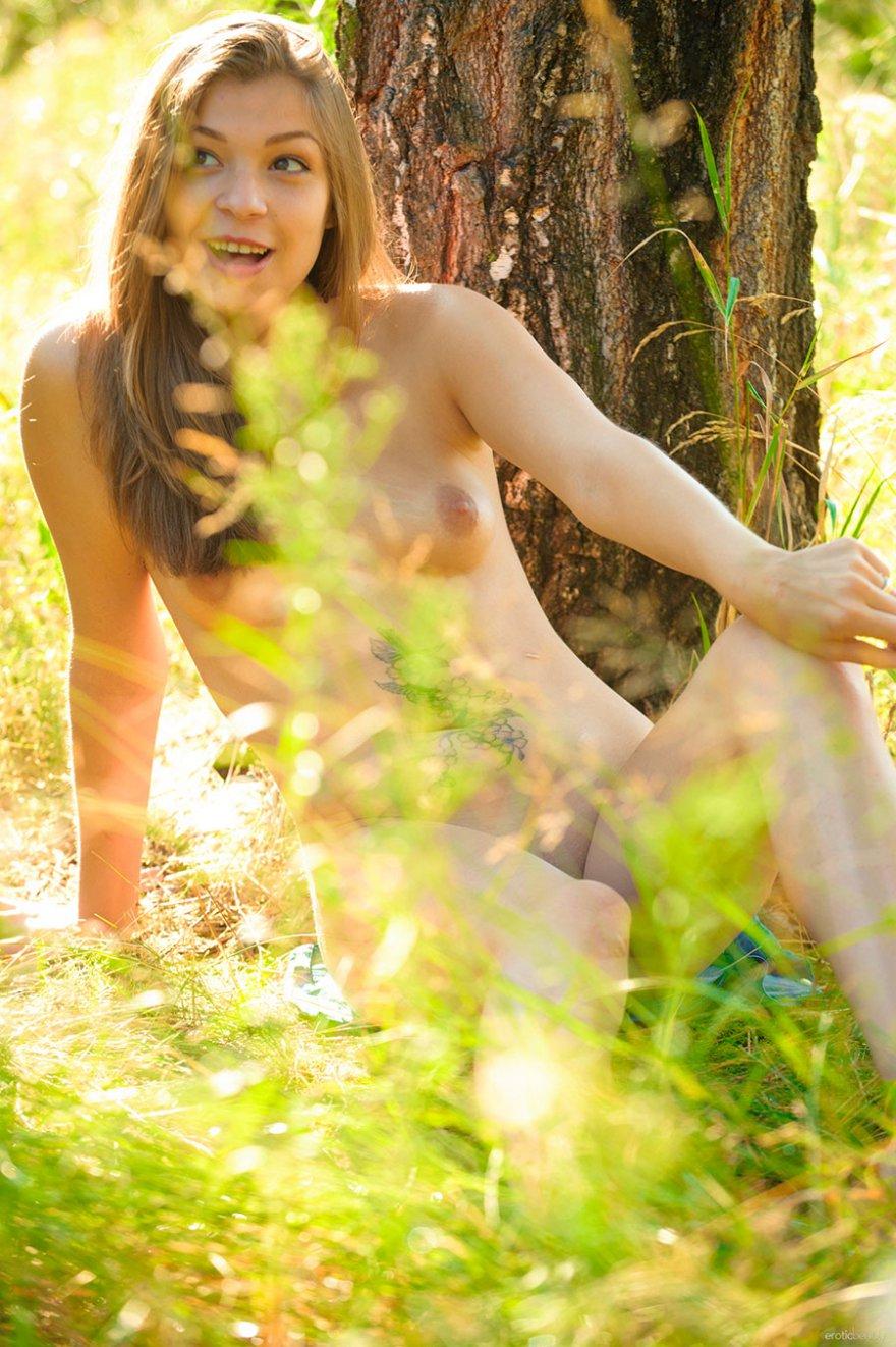 Секс фото блондинки с наколками на животе под деревом