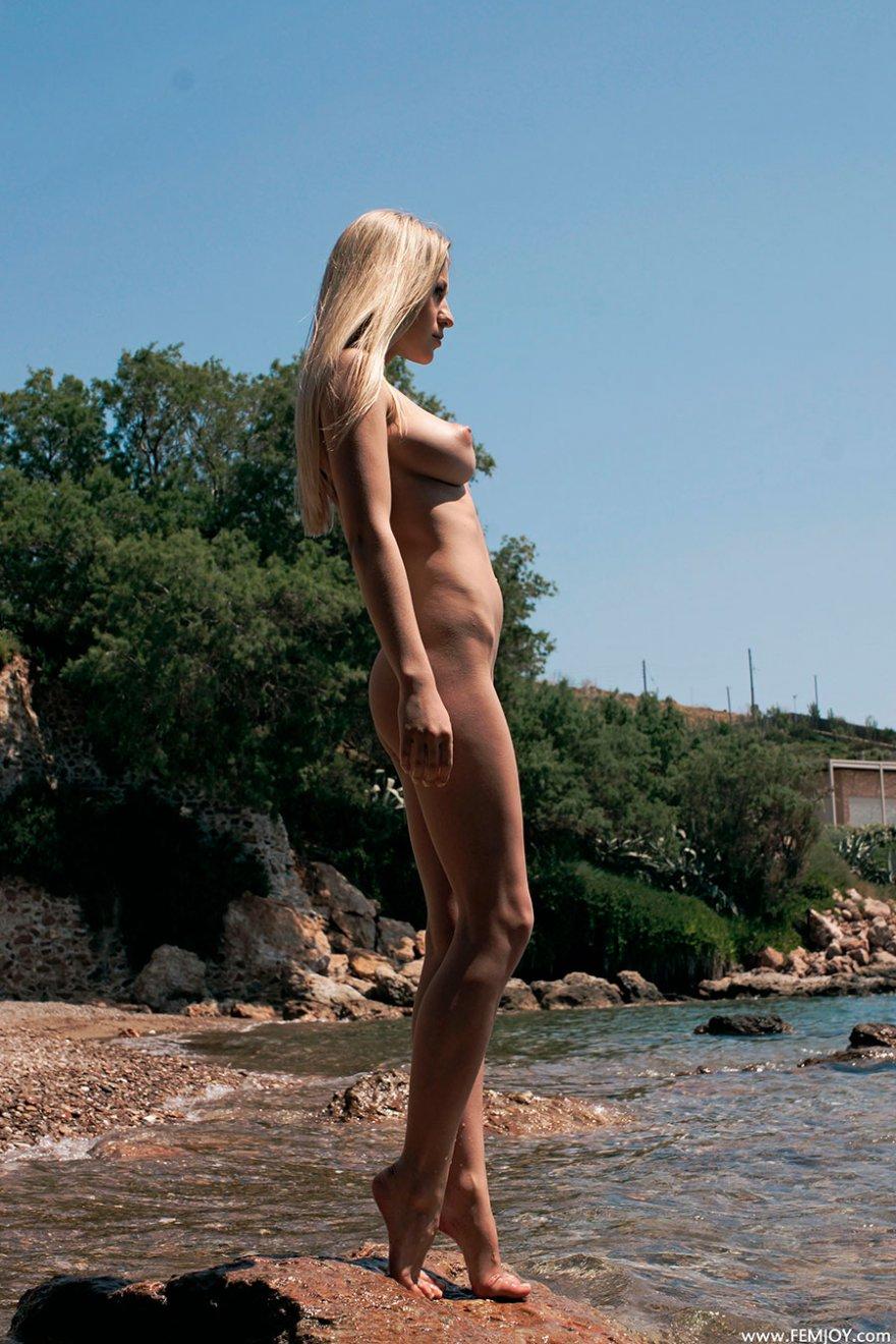 Блондинка в черном купальнике спускается к морю