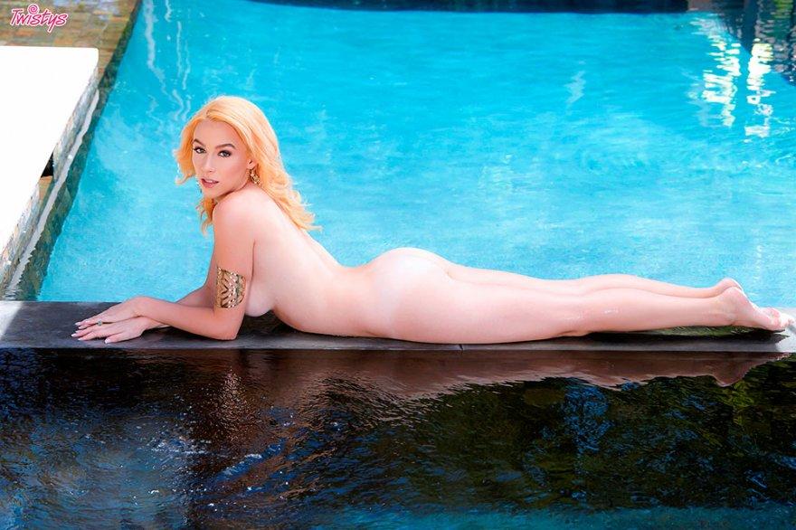 Эротика блондиночки с браслетом на руке около бассейна