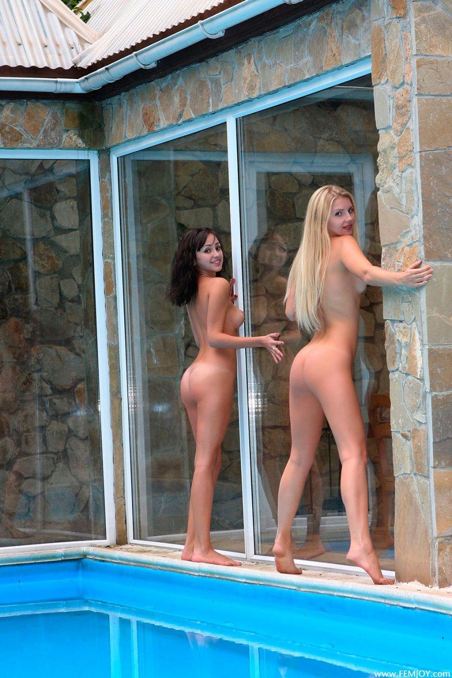 Две девушки - блондинка и брюнетка возле бассейна