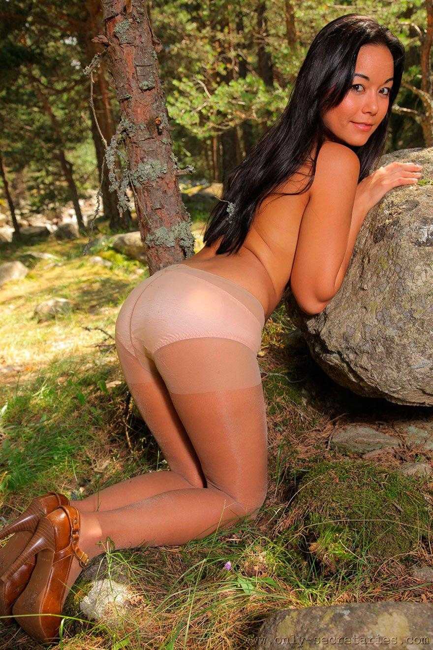 Девушка в колготках позирует в лесу