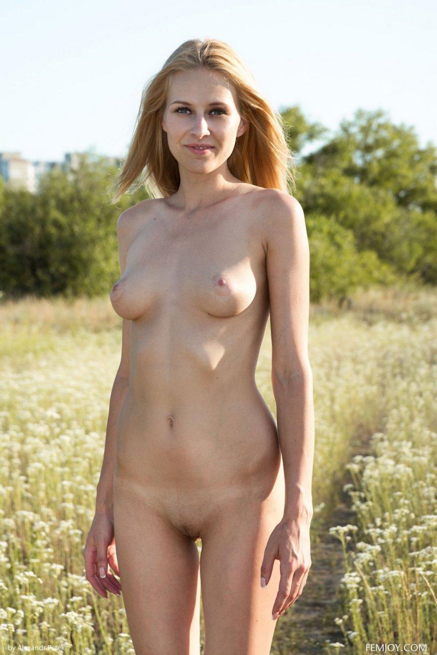 Нагая светловолосая девушка в лесу
