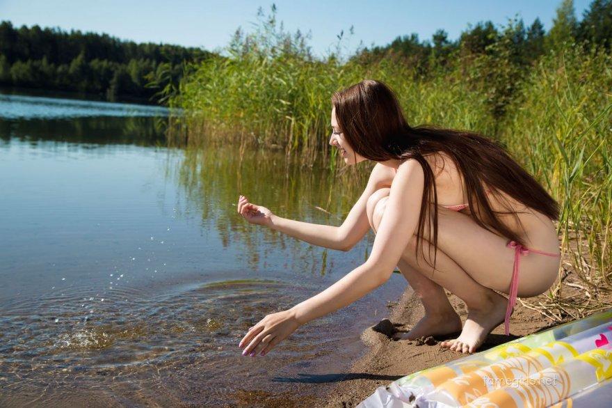 Голая брюнетка плавает на надувном матрасе