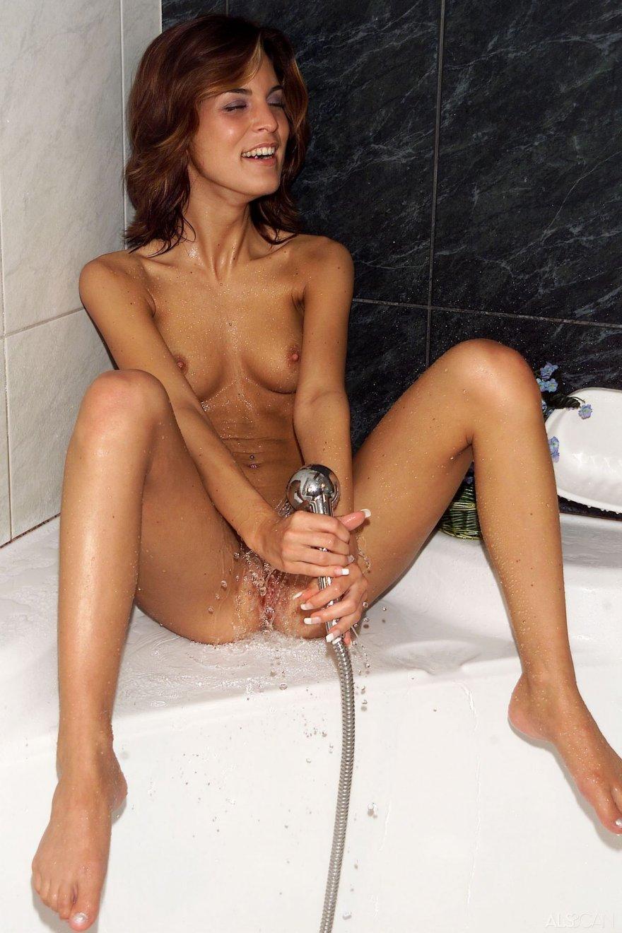 Женщина в мокрых трусах фотографируется под струями воды
