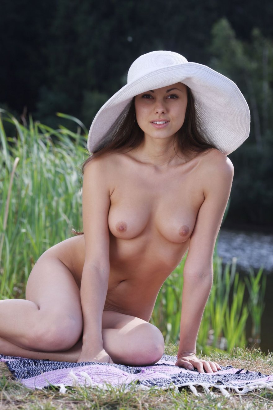 Девка в шляпе фотографируется вблизи от реки